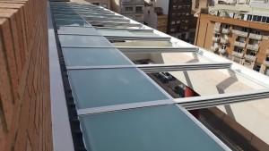 Cerramiento de terraza compuesto por techo de aluminio retráctil motorizado y frontal de cortina de vidrio totalmente plegable